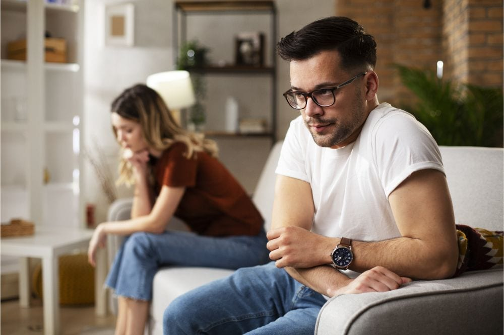 Couple at home after having a fight. Sad depressed man sitting on sofa..