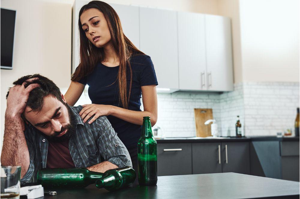 woman comforting her alcoholic husband