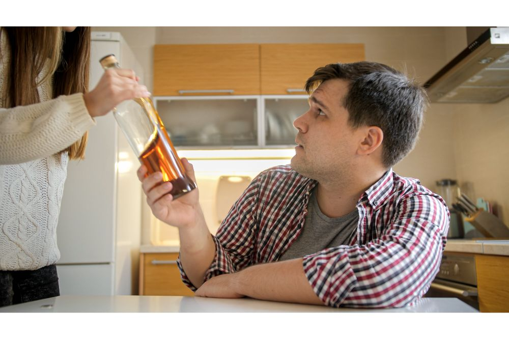 woman taking bottle of alcohol from male alcoholic drinking spirits on kitchen