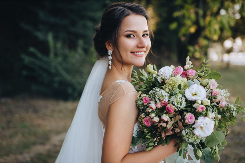 A beautiful bride stands on nature in greenery with a large bouquet